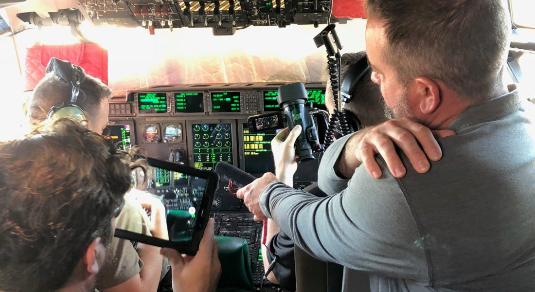 Soldier being recorded by others while using controls inside of plane
